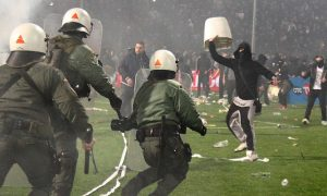 PAOK fans clash with riot police during a Greek Cup semifinal match between PAOK and champion Olympiakos at the Toumba stadium in the northern Greek city of Thessaloniki, Wednesday, March 2, 2016. The match has been stopped in the final minute after home fans threw flares onto the pitch and ran onto the field to clash with riot police. The first-leg match was stopped in the 90 minute as Olympiakos led 2-1. (InTime Sports via AP)  GREECE OUT